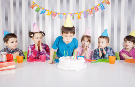Cute boy blowing candles on birthday cake.