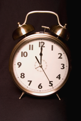 Old-fashioned iconic metal alarm clock face displays twelve o'clock as viewed head-on.